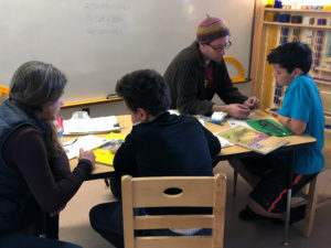 two mentor-student pairs work indoors with notebooks