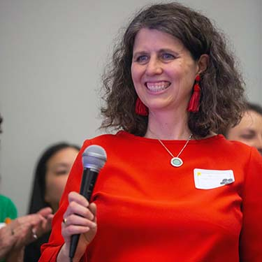 Woman (Jennifer Fries) in red shirt holding a microphone and wearing a name tag.